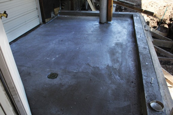 """The walls are 4"""" higher than the floor to accommodate 2"""" of rigid foam insulation and 2"""" of radiant floor thin slab concrete.  Note the air intake for the indoor woodstove."""