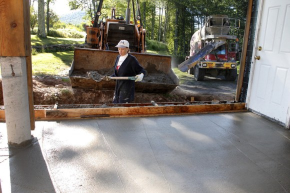 Deb shoveling concrete, helping to put the finishing touches on the foundation pour.