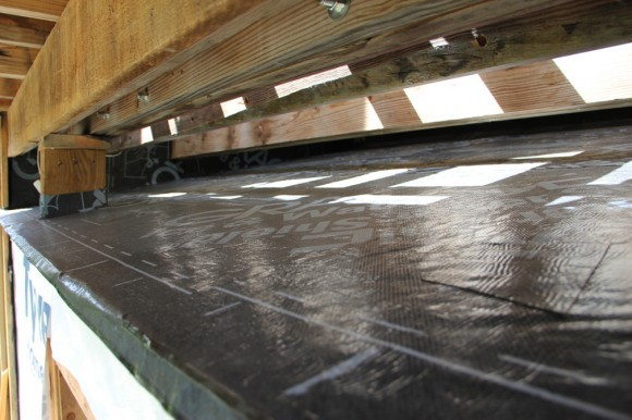 The new roof had to be slipped in under the upper deck. I had to remove most of the deck boards to do this.     Very expensive waterproof underlayment by WR Grace   was used. Later I added metal roofing on top of this.