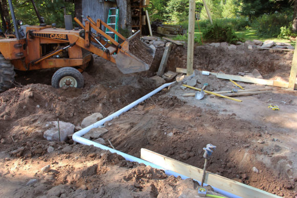 """At the end of August my next project """"The Pavilion"""" was well under way. 4"""" PVC and 2"""" stone surround the slab for good drainage. Drains to daylight."""